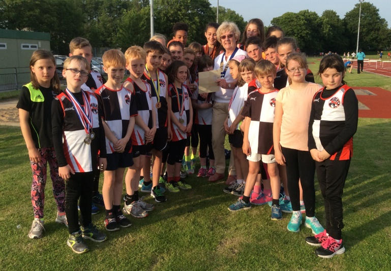 Northern Athletics President Jean Simpson MBE with young athletes from her club Bury AC